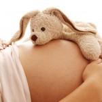 Schwangere, entspannt mit Stofftier, Kinderwunsch